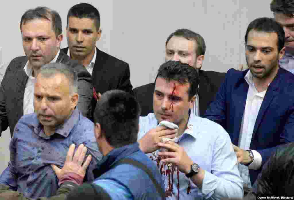 Zoran Zaev, the head of a newly formed coalition in Macedonia that said it was trying to assert its right to govern by electing the new parliament speaker, is escorted from parliament on April 27 with blood streaming from his head after protesters stormed the building and assaulted him. (Reuters)