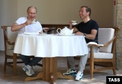 Russian President Vladimir Putin and then-Prime Minister Dmitry Medvedev drink tea during breakfast at the state residence in Sochi in 2015.