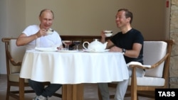 Russian President Vladimir Putin (left) and Prime Minister Dmitry Medvedev drink tea during breakfast at the Bocharov Ruchei state residence in Sochi on August 30.