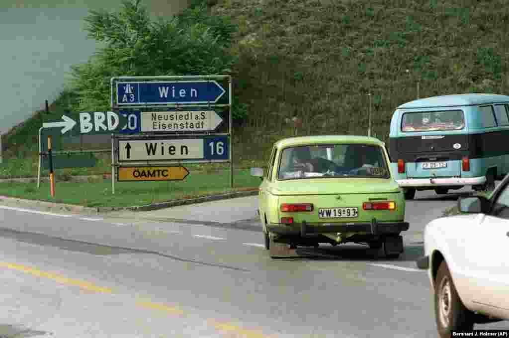 An East German car follows a handwritten sign for West Germany, orBundesrepublik Deutschland (BRD).