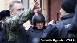 Oleg Sokolov (center), dressed in a bulky bullet-proof vest and helmet, was brought on November 15 to his apartment in St. Petersburg, where the head of his alleged victim was found.