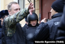 On November 15, Oleg Sokolov (center), dressed in bullet-proof clothing, was brought to his apartment in St. Petersburg, where his alleged victim's head had been found.