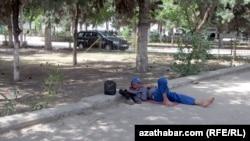 Aşqabad, yol çəkilişində işləyən fəhlə kölgədə istirahət edir, 1 iyun 2015