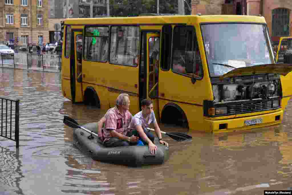 Чоловік на гумовому човні допомагає людям пересуватися затопленою частиною у місті Львові після сильної зливи, 17 серпня 2018 року. БІЛЬШЕ ПРО ЦЕ