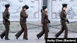 КНДР, женщины-пограничницы идут вдоль берега реки на корейской стороне границы с Китаем