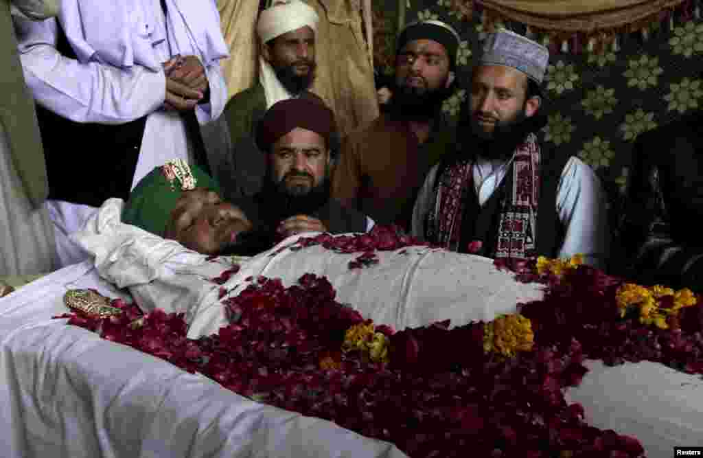 Supporters and family members of Mumtaz Qadri sit near his body after his execution in Rawalpindi, Pakistan, on February 29. Qadri killed the governor of Punjab Province over his call to reform the country's strict blasphemy laws. (Reuters/Faisal Mahmood)