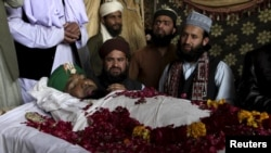 Supporters and family members of Mumtaz Qadri sit near his body after his execution in Rawalpindi, Pakistan, on February 29. Qadri was hanged for murdering a provincial governor in 2011 after the official called for reform of the country's strict blasphemy laws.