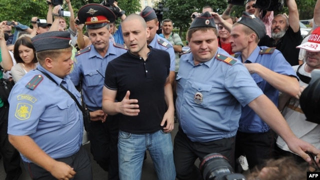 Police officers detain Russian opposition leader Sergei Udaltsov (center) in Moscow on August 9.