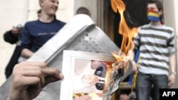 Un protestatar dînd foc unui ziar cu portretul lui Vladimir Voronin în apropierea Parlamentului