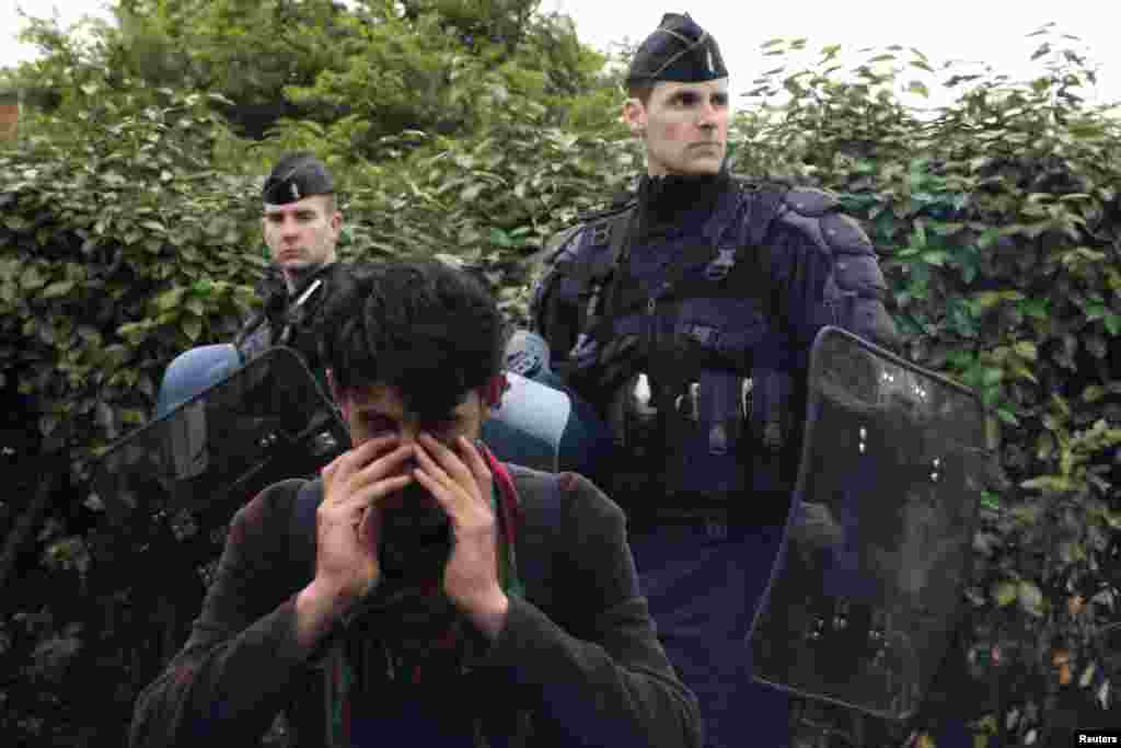 An Afghan immigrant wipes his eyes as French police evacuate him and others from an improvised camp in Calais on May 28. (Reuters/Pascal Rossignol)