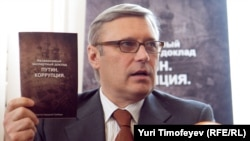 """Former Prime Minister Mikhail Kasyanov holds up a copy of the report """"Putin. Corruption,"""" at its presentation on March 28."""