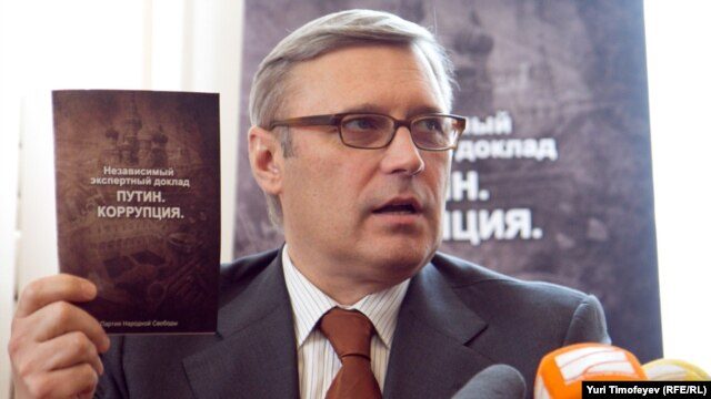 "Former Prime Minister Mikhail Kasyanov holds up a copy of the report ""Putin. Corruption,"" at its presentation on March 28."