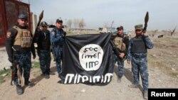 Іракські силовики тримають догори дригом на знак зневаги прапор угруповання «Ісламська держава», який вони здерли у визволеній частині західного Мосула, 27 лютого 2017 року