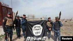 Іракські силовики тримають догори дригом на знак зневаги прапор угруповання «Ісламська держава», який вони здерли у визволеній частині Мосула, 27 лютого 2017 року