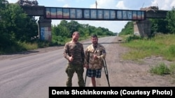 "Denis Shchinkorenko (left) and Andrei Kamayev pose near a bridge painted with the word ""Novorossia"" in September 2015 in eastern Ukraine."