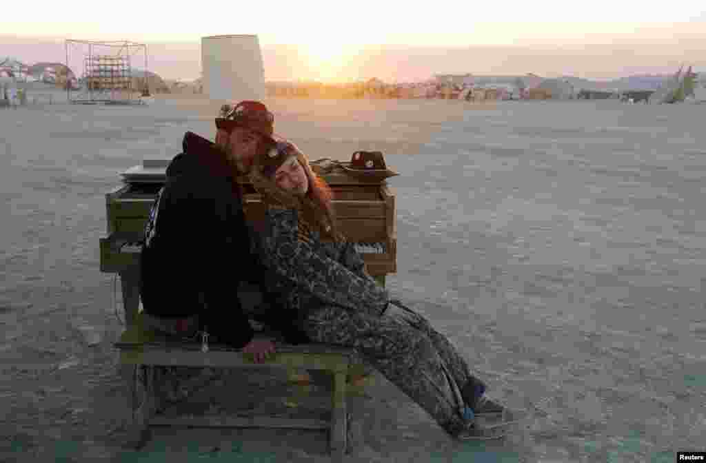 A couple rest at a piano in the desert at sunrise during the 2013 Burning Man arts and music festival.