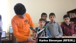 Vazgen Hovhannisian (left), a 16-year-old computer-game designer, works on a robot during a computer club meeting in the Armenian village of Aygek.