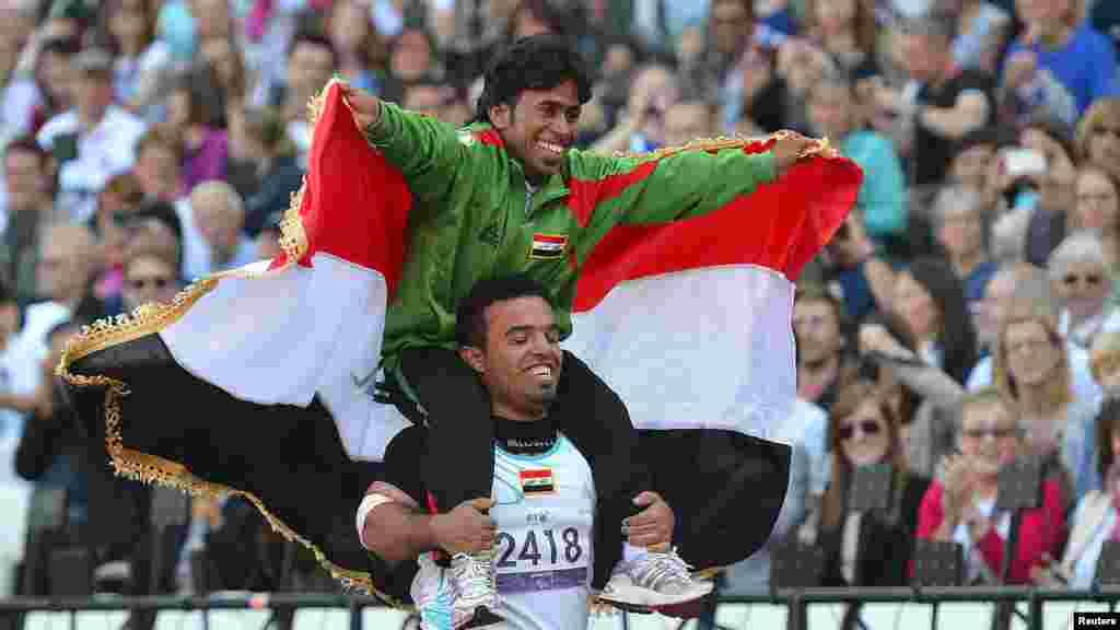 Ahmed Naas of Iraq (top) embraces Wildan Nukhailawi of Iraq after the end of a men's javelin final at the Olympic Stadium in London's Olympic Park.