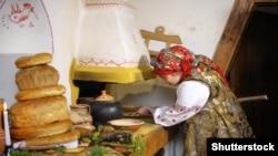 Жінка в українському традиційному вбранні ставить казан у піч для приготування куті – різдвяної страви