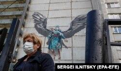 Дәрігерлер ерлігіне арналған граффити салынған ғимарат жанынан өтіп бара жатқан әйел. Мәскеу облысы, мамыр 2020 жыл.