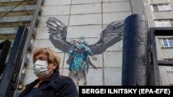 Дәрігерлер ерлігі туралы граффити салынған ғимаратын жанынан өтіп бара жатқан әйел. Мәскеу облысы, мамыр айы 2020 жыл.