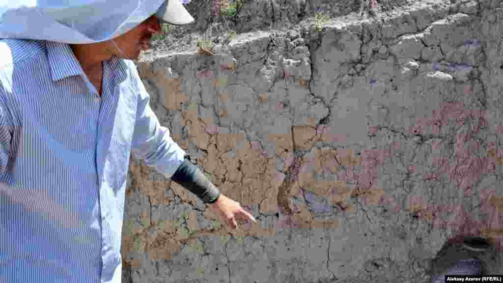 Археолог қабырғаның түйіскен тұсында қалып қалған кірпіш қалдығын көрсетіп жатыр.