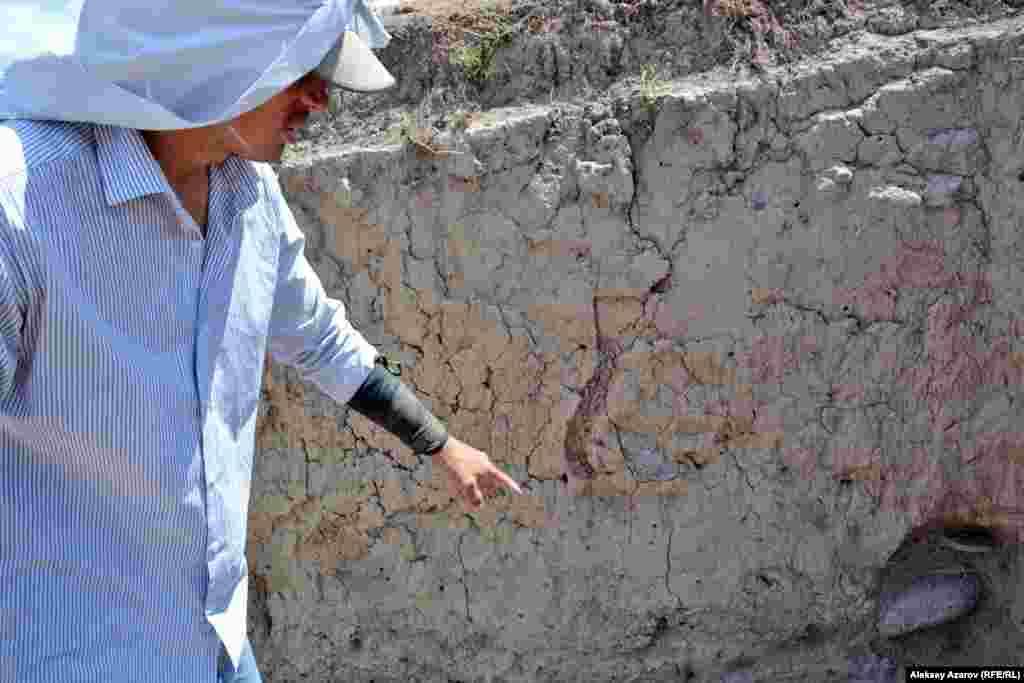 Археолог показывает сохранившуюся кирпичную кладку, которая видна на срезе.