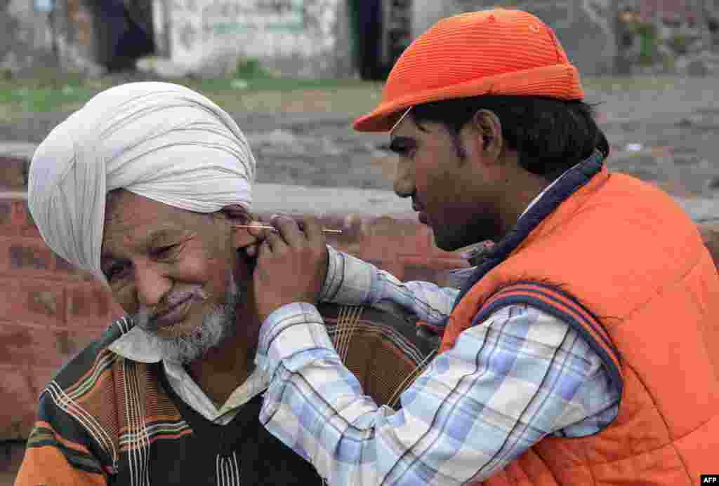 Indian ear cleaner Sunil Kumar (right) tends to a customer on the road in Amritsar. Ear cleaners, or kaan saaf wallahs as they are locally known, are a common sight in Indian cities where customers pay to have wax and dirt scraped from inside their ears. (AFP/Narinder Nanu)