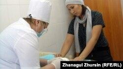 Медбике үш айлық сәбиге вакцина салып жатыр. Ақтөбе, 25 қаңтар 2012 жыл. (Көрнекі сурет)
