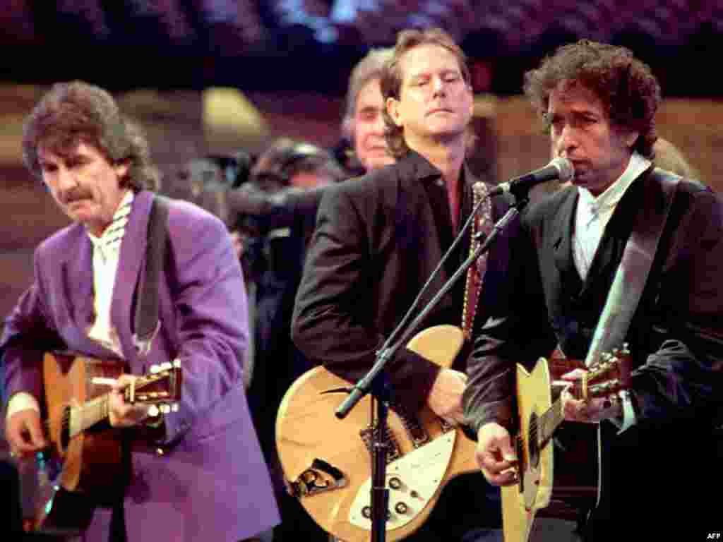 Dylan (right), George Harrison (left), Johnny Cash, and Roger McGuinn celebrate the 30th anniversary of Dylan's debut album in October 1992.