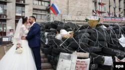 Новобрачные целуются у баррикады в центре города Донецка. 2 мая 2014 года.