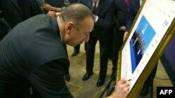 Turkey -- Azerbaijani President Ilham Aliyev signs a print of the G20-Turkey family photo at the Group of 20 (G20) summit, in the Mediterranean resort city of Antalya, November 15, 2015