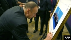 Turkey -- Azerbaijani President Ilham Aliyev signs a print of the G20-Turkey family photo at the Group of 20 (G20) summit, in the Mediterranean resort city of Antalya, November 15, 2015