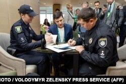 Поліція складає протокол Володимиру Зеленському, який показав бюлетень, порушивши правила голосування. Зеленському загрожує штраф. 21 квітня 2019 року