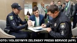 Полиция составляет протокол Владимиру Зеленскому, который показал бюллетень, нарушив правила голосования. Зеленскому грозит штраф. 21 апреля 2019 года