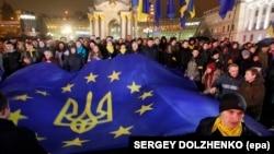 Еуроодақ туын ұстап тұрған наразылық шеруіне қатысушылар. Киев, қаңтар айы 2014 жыл