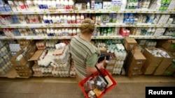 Покупательница в отделе молочной продукции супермаркета. Иллюстративное фото.