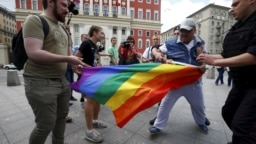 Protesters try to tear a rainbow flag during an LGBT community rally in central Moscow in May 2015.