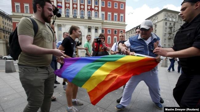 Антигейские активисты отбирают радужный флаг ЛГБТ-сообщества в центре Москвы. 30 мая 2015 года.
