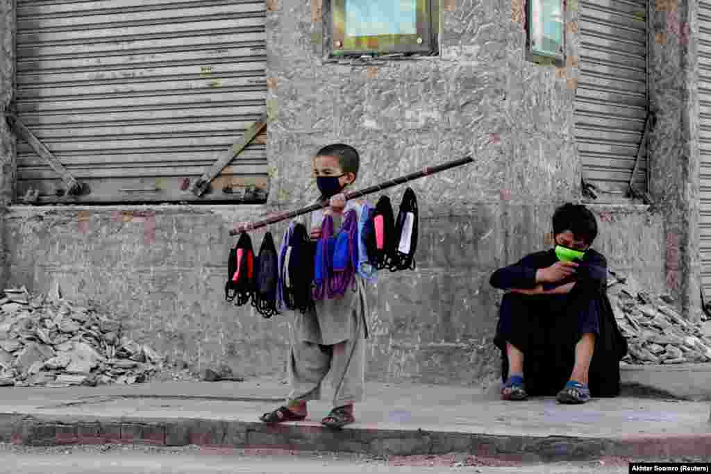 Seven-year-old Uzbillah stands with face masks on a stick selling them with his brother at the corner of a street during a lockdown in Karachi on March 31. (Reuters/Akhtar Soomro)