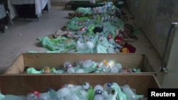 Bottles containing ice cover the bodies of people whom protesters say were killed by pro-regime forces in Deraa on June 26.