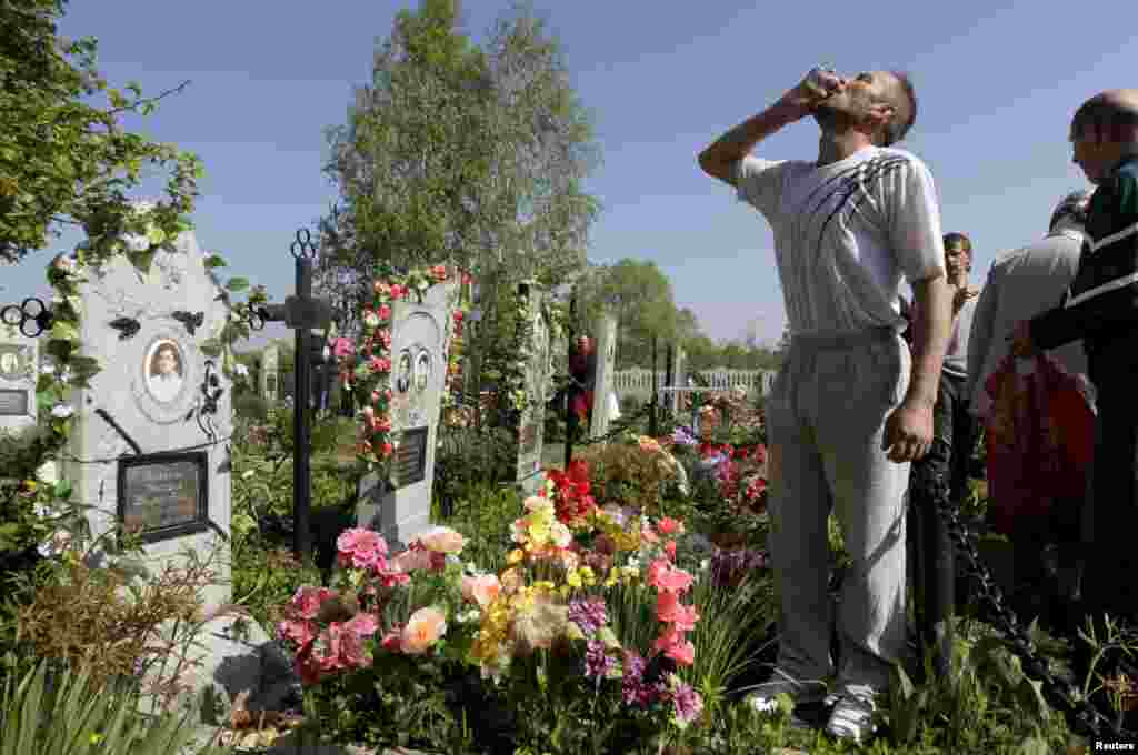 A man drinks vodka at a grave during Orthodox Easter in the Belarusian village of Pogost. Villagers in southern parts of Belarus visit their relatives' graves during Easter celebrations. (Reuters/Vasily Fedosenko)