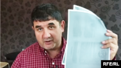 RFE/RL Uzbek journalist Shukrat Babajanov holds the document showing that the land on which the house is located was granted to him by the State in 1998.