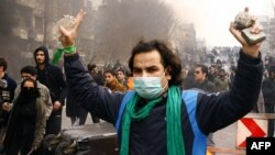 An Iranian opposition supporter gestures during clashes with security forces in Tehran on December 27.