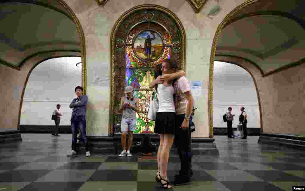 A couple in front of a stained glass panel at the Novoslobodskaya metro station