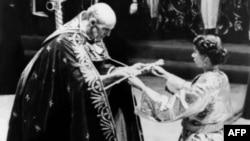 Архиепископ Кентерберийский протягивает королеве Елизавете меч. Церемония коронации в Вестминстерском аббатстве, 2 июля 1953 года.