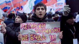 "A government supporter holds a sign saying, ""Russian Journalist: Don't Be A Prostitute!!!"" at a pro-Kremlin rally in Moscow on December 12."