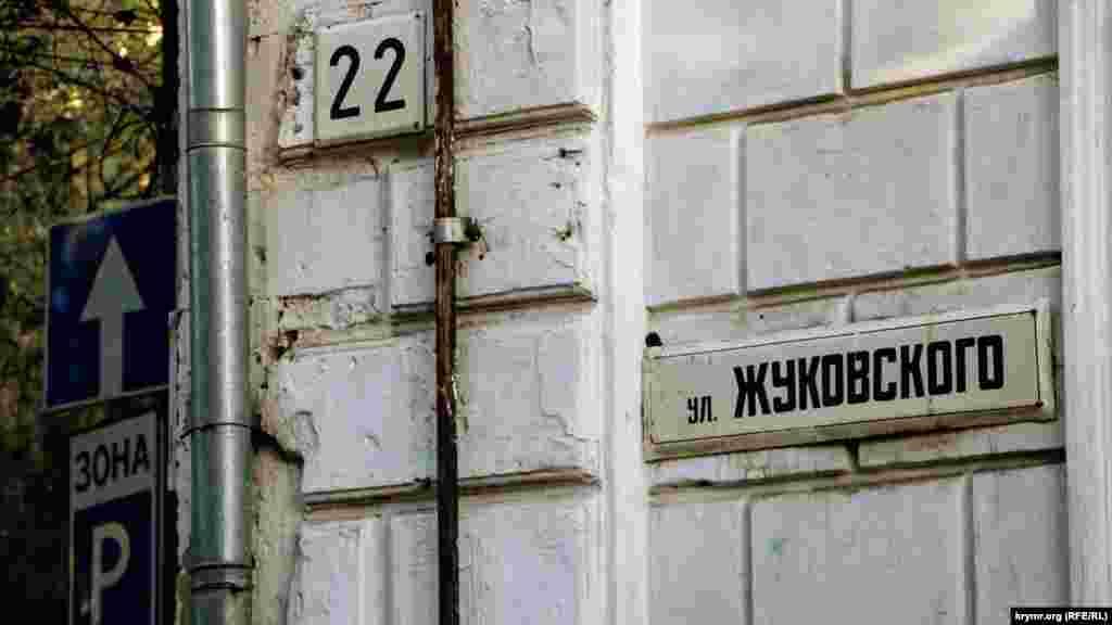 Табличка с названием улицы и номером дома на углу здания