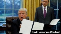 U.S. President Donald Trump holds up the executive order on withdrawing from the Trans-Pacific Partnership trade deal at the White House on January 23.