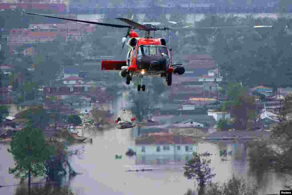 A helicopter crew helps a resident flee a flooded neighborhood on August 30.